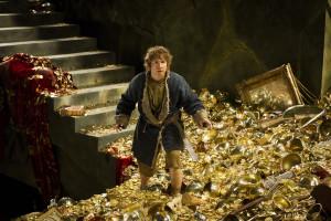 Beztroski Bilbo biega sobie po górze złota w obecności smoka.
